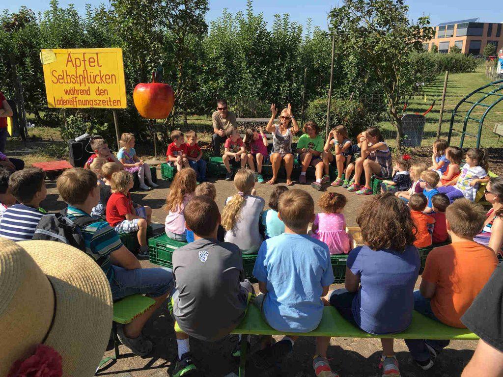 Viele Kinder sitzen im Stuhlkreis auf dem Appel Happel Hof, während Frau Happel etwas erklärt