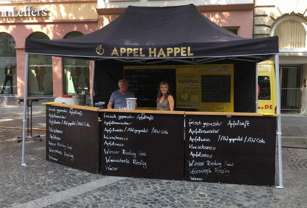 Frau Happel steht hinter der Theke des schwarzen Appel Happel Zelts auf dem Mainzer Domplatz