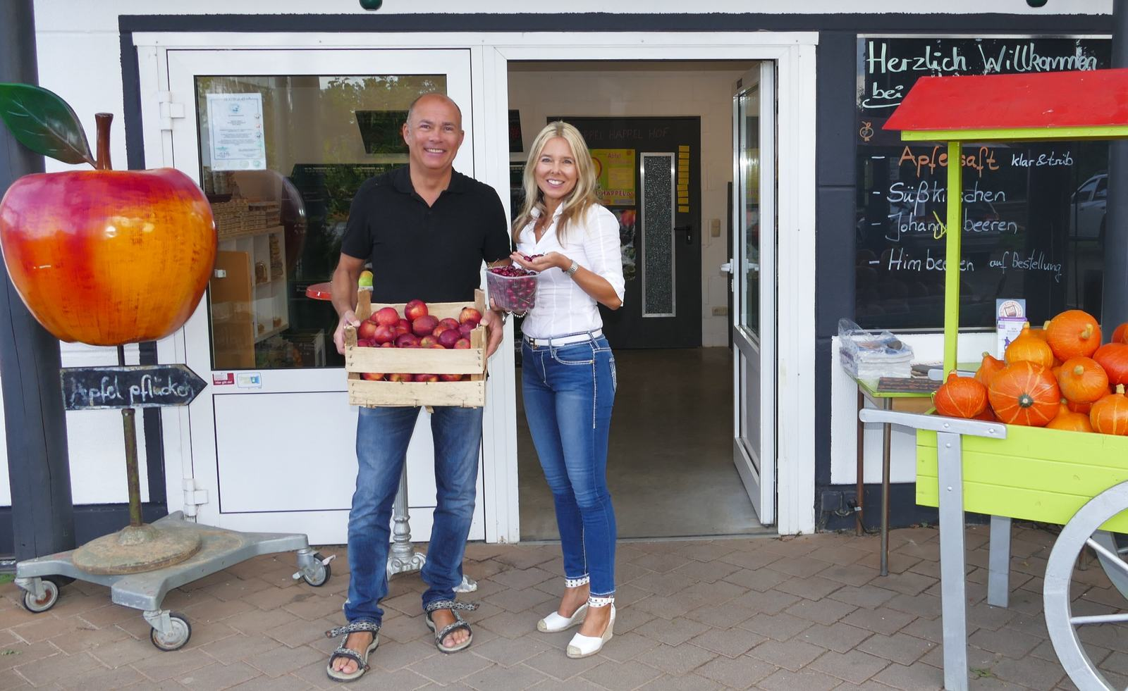 Die Inhaber des Appel Happel Hofs stehen vor dem Bauernladen und halten Äpfel und Kirschen in den Händen.
