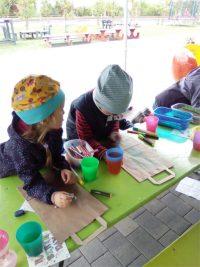 Kinder sitzen an einem Tisch und bemalen Apfeltüten