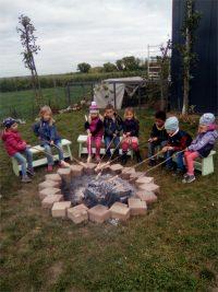 Kinder sitzen im Stuhlkreis um ein Lagerfeuer und machen Stockbrot