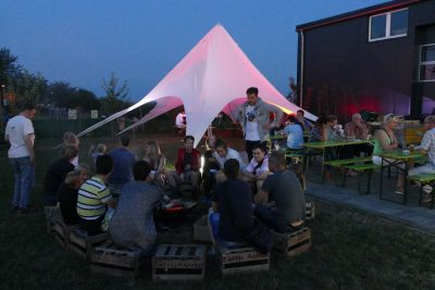 Erwachsene sitzen in der Nacht um Lagerfeuer. Im Hintergrund ein weißes Zelt