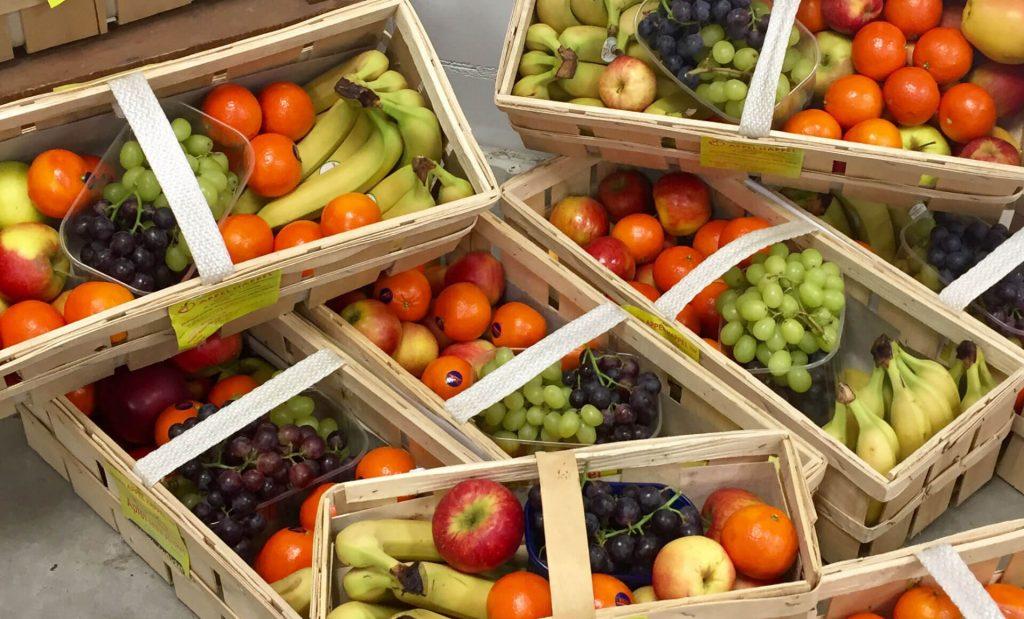 Gefüllt Obstkörbe für den Appel Happel Firmenlieferservice sind zu sehen. Gefüllt mit frischen Äpfeln, Trauben, Mandarinen und Bananen