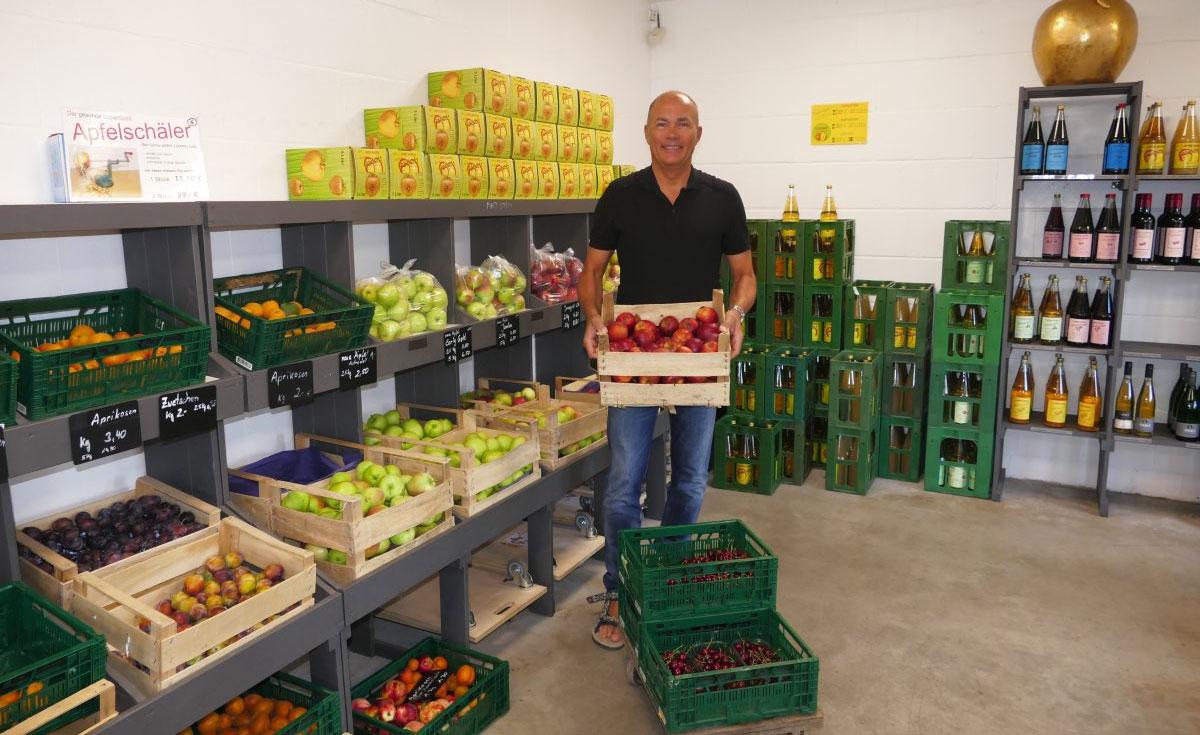 Der Inhaber Herr Happel steht im Bauernladen des Appel Happel Hofs und trägt eine Kiste mit Äpfeln